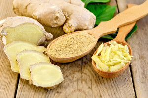Grated and ground ginger in two wooden spoons, ginger root, green leaves on the wooden board